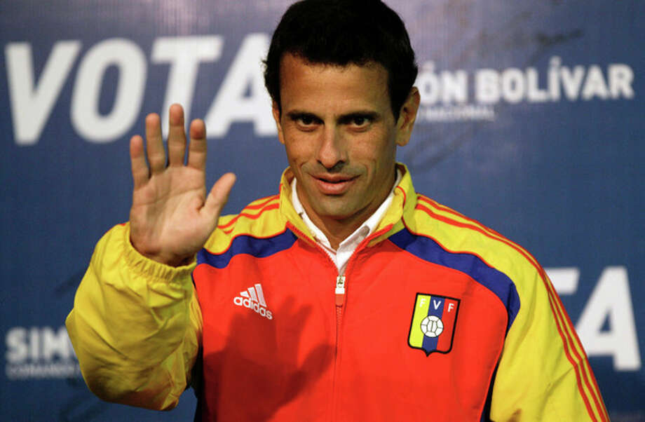 Opposition presidential candidate Henrique Capriles waves as he arrives to a news conference in Caracas, Venezuela, Saturday, April 13, 2013. Capriles is running against ruling party candidate and acting President Nicolas Maduro in Sunday's special presidential election. (AP Photo/Fernando Llano) / AP