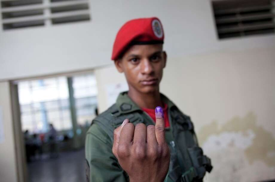 A presidential guard soldier shows his finger marked with ink after voting in the presidential election at a polling station in Caracas, Venezuela, Sunday, April 14, 2013. Interim President Nicolas Maduro, who served as the late Hugo Chavez's foreign minister and vice president, is running against opposition candidate Henrique Capriles. (AP Photo/Ramon Espinosa) / AP