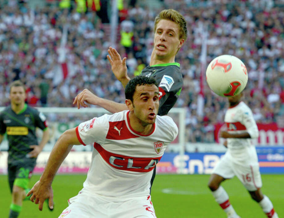 Stuutgart's Cristian Molinaro, front, challenges for the ball with Moenchengladbach's Patrick Herrmann. top, during the German Bundesliga soccer match between VfB Stuttgart and Borussia Moenchengladbach in Stuttgart, southern Germany Sunday, April 14, 2013. (AP Photo/dpa, Bernd Weissbrod) / dpa