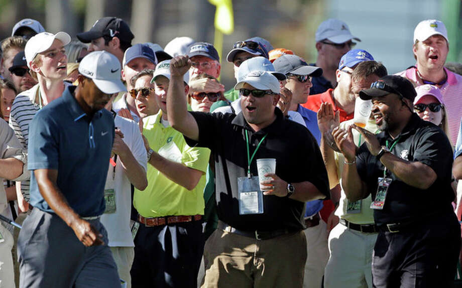 Tiger Woods is cheered by spectators as he walks up the 17th fairway during the third round of the Masters golf tournament Saturday, April 13, 2013, in Augusta, Ga. (AP Photo/David Goldman) / AP