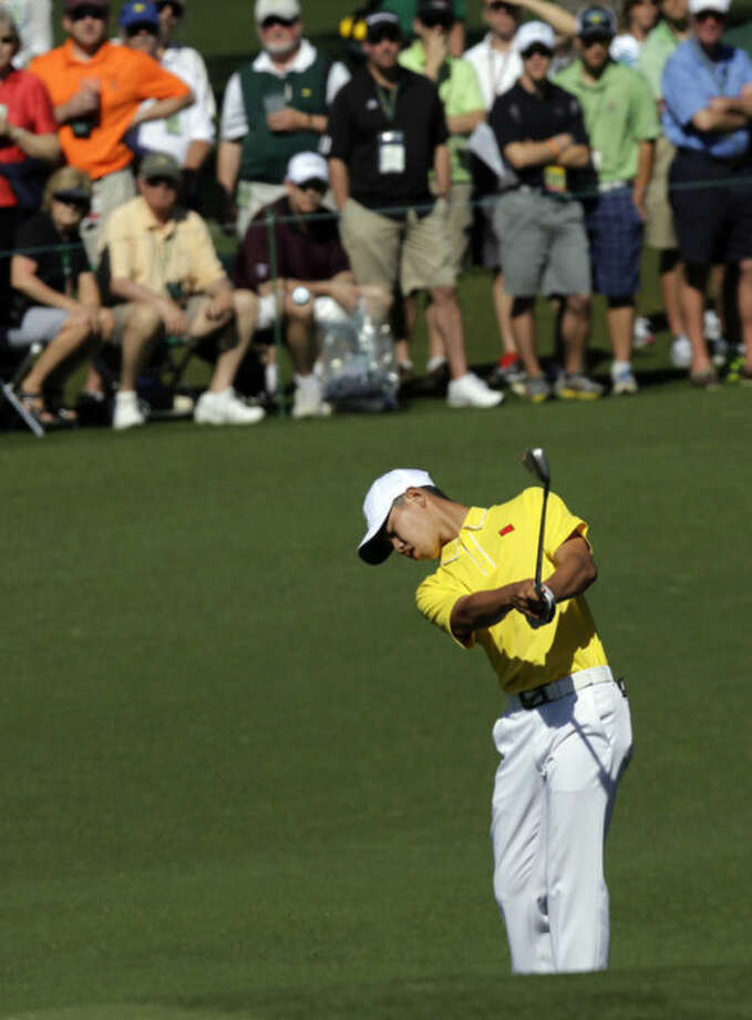 Amateur Guan Tianlang, of China, chips to the second green during the third round of the Masters golf tournament Saturday, April 13, 2013, in Augusta, Ga. (AP Photo/David J. Phillip)
