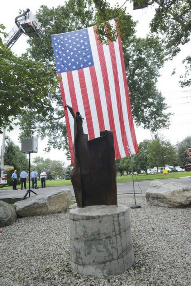 An artifact from the World Trade Center is unveiled as a statue on the grounds of St. Pauls' on the Green Sunday. hour photo/matthew vinci