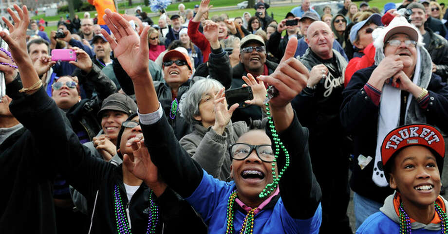 Connecticut fans reach for beads during a parade celebrating the women's basketball team's national championship victory in the NCAA college tournament in Hartford, Conn., Sunday, April 14, 2013. (AP Photo/Jessica Hill) / FR125654 AP