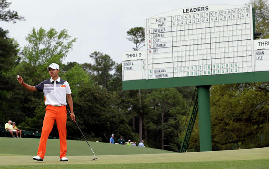 Amateur Guan Tianlang, of China, holds up his ball after putting out on the 18th green during the fourth round of the Masters golf tournament Sunday, April 14, 2013, in Augusta, Ga. (AP Photo/David J. Phillip) / AP