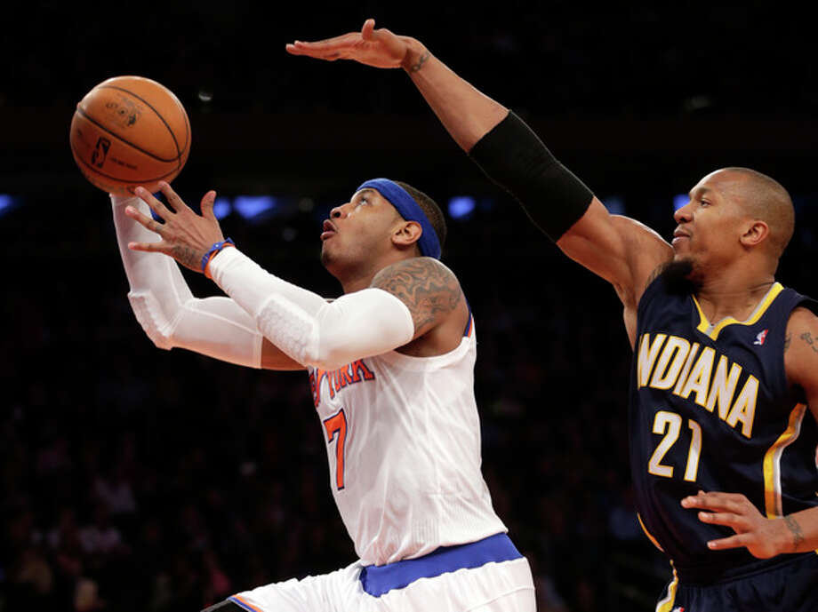 New York Knicks' Carmelo Anthony, left, shoots past Indiana Pacers' David West during the second half of the NBA basketball game, Sunday, April 14, 2013, in New York. The Knicks won 90-80. (AP Photo/Seth Wenig) / AP