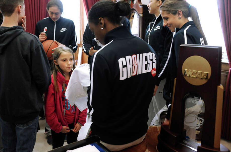 Catalina Brown, 9, has a shirt autographed by Connecticut's Brianna Banks, center, as Caroline Doty, right, looks on during a meet-and-greet in Gov. Dannel P. Malloy's office before a parade celebrating the women's basketball team's national championship victory in the NCAA college tournament in Hartford, Conn., Sunday, April 14, 2013. (AP Photo/Jessica Hill) / FR125654 AP