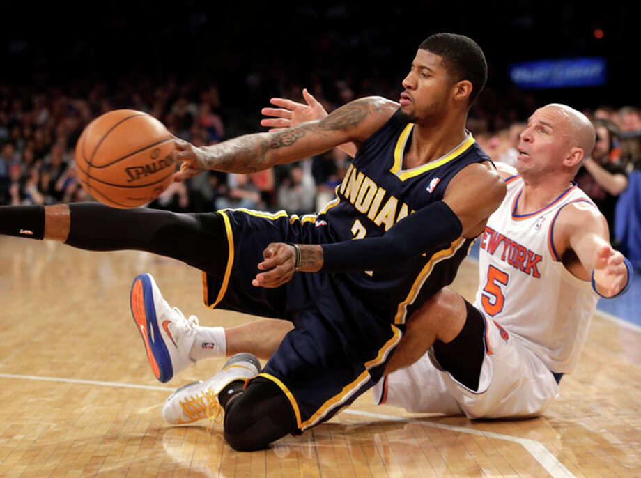 Indiana Pacers' Paul George, left, passes the ball after tumbling to the court with New York Knicks' Jason Kidd during the first half of the NBA basketball game, Sunday, April 14, 2013, in New York. (AP Photo/Seth Wenig) / AP