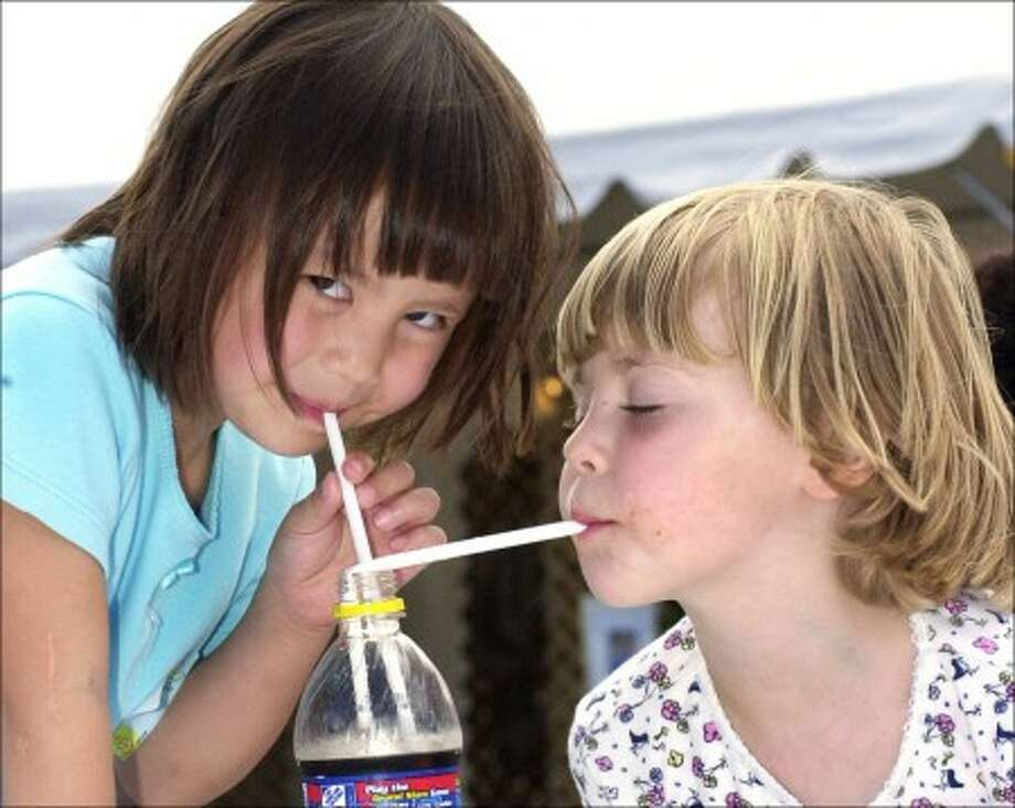 From left, Maeve Stewart 5, from New Jersey and her cousin Valerie Bolzar 4, share a cold drink at the Festival Italiano in Westport on Saturday afternoon..photo matthew vinci
