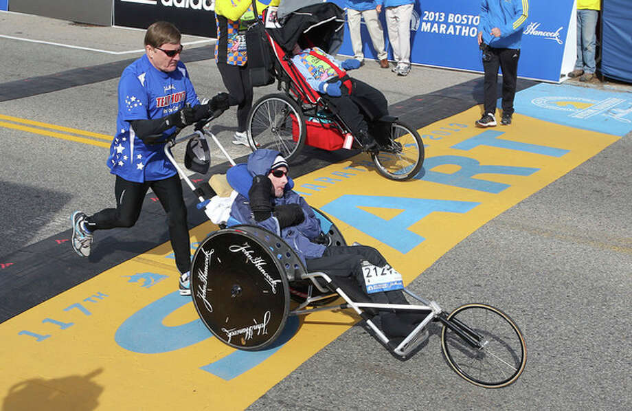 Dick Hoyt, left, and his son, Rick, start of the 117th running of the Boston Marathon, in Hopkinton, Mass., Monday, April 15, 2013. (AP Photo/Stew Milne) / FR56276 AP