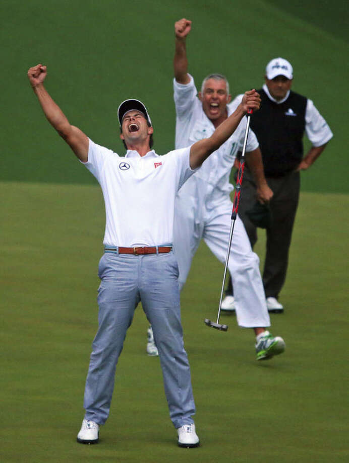 Adam Scott and his caddie Steve Williams reacts to his putt dropping on the second hole of a playoff to win the Masters golf tournament, Sunday, April 14, 2013, in Augusta. Runner-up Angel Cabrera watches in the background. Scott became the first Australian to win the Masters. (AP Photo/Atlanta Journal-Constitution, Curtis Compton)