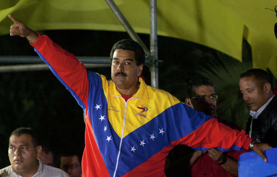 Venezuela's newly elected President Nicolas Maduro celebrates his victory after the official results of the presidential elections were announced, at the Miraflores Palace in Caracas, Venezuela, late Sunday, April 14, 2013. Maduro, Hugo Chavez's hand-picked successor, won a razor-thin victory in Sunday's special presidential election, edging the opposition leader Henrique Capriles by only about 300,000 votes, electoral officials announced. (AP Photo/Ramon Espinosa) / AP