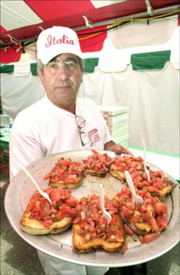 Oswald Ruggierri cooks brushetta made with homemade bread tomato, basil, garlic and olive oil for Italia Restuarant at the Italiano Festival in Westport. ..photo matthew vinci