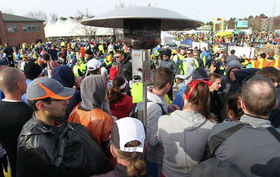 Runners gather around a portable heater in the athletes village prior to the start of the 117th running of the Boston Marathon, in Hopkinton, Mass., Monday, April 15, 2013. (AP Photo/Stew Milne) / FR56276 AP