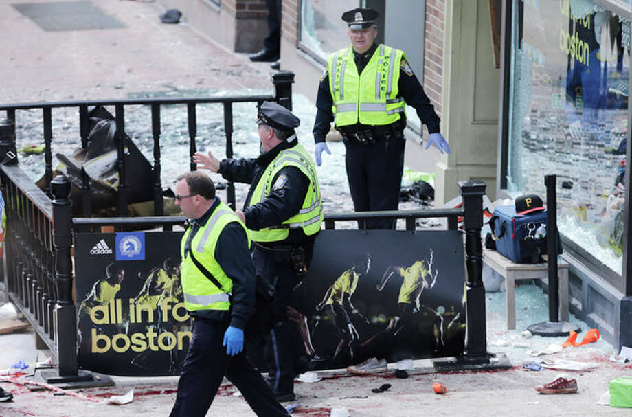 Boston police clear an area following an explosion near the finish line of the 2013 Boston Marathon in Boston, Monday, April 15, 2013. Two explosions shattered the euphoria of the Boston Marathon finish line on Monday, sending authorities out on the course to carry off the injured while the stragglers were rerouted away from the smoking site of the blasts. (AP Photo/Charles Krupa) / AP