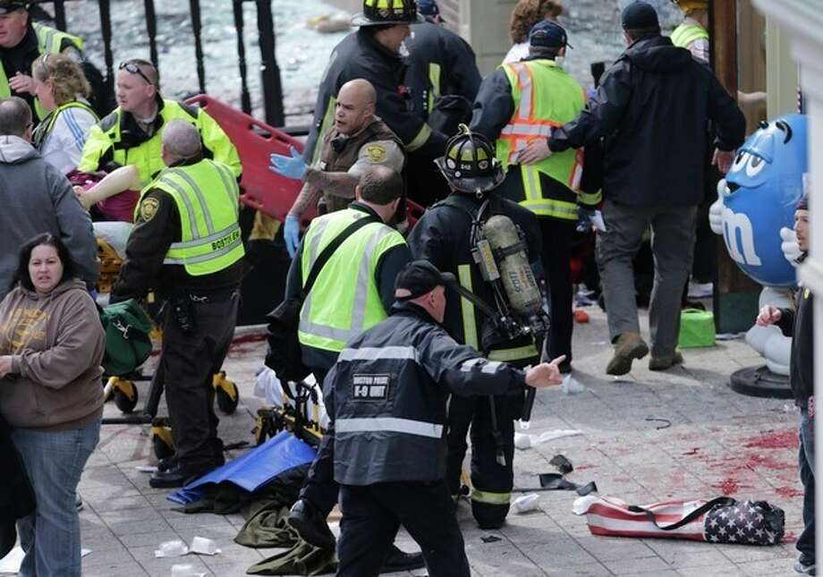 Medical workers aid injured people at the finish line of the 2013 Boston Marathon following an explosion in Boston, Monday, April 15, 2013. (AP Photo/Charles Krupa) / AP