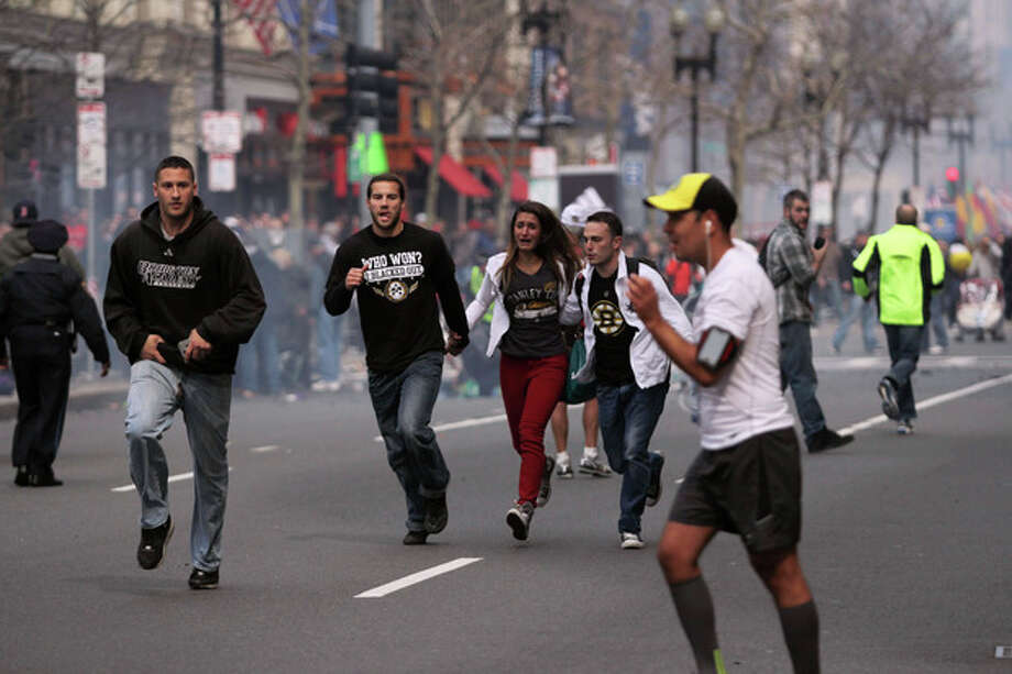 In this photo provided by The Daily Free Press and Kenshin Okubo, people react to an explosion at the 2013 Boston Marathon in Boston, Monday, April 15, 2013. Two explosions shattered the euphoria of the Boston Marathon finish line on Monday, sending authorities out on the course to carry off the injured while the stragglers were rerouted away from the smoking site of the blasts. (AP Photo/The Daily Free Press, Kenshin Okubo) MANDATORY CREDIT / The Daily Free Press
