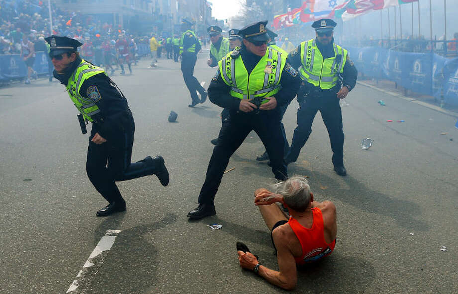 Bill Iffrig, 78, lies on the ground as police officers react to a second explosion at the finish line of the Boston Marathon in Boston, Monday, April 15, 2013. Iffrig, of Lake Stevens, Wash., was running his third Boston Marathon and near the finish line when he was knocked down by one of two bomb blasts. (AP Photo/The Boston Globe, John Tlumacki)