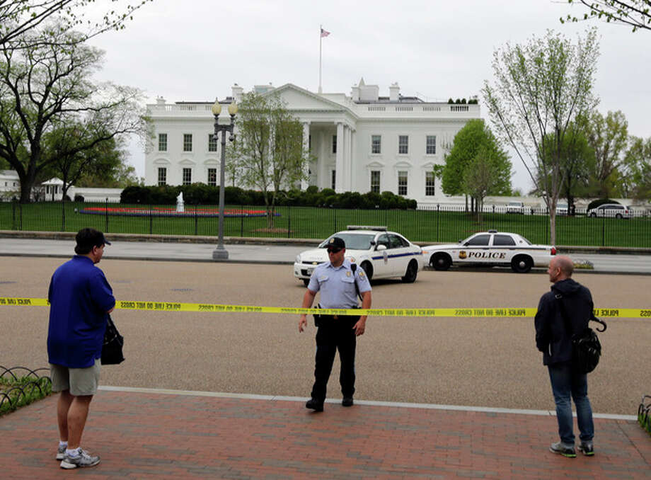 People stand behind police tape after law enforcement closed down Pennsylvania Avenue in front of the White House Monday, April 15, 2013 in Washington. (AP Photo/Alex Brandon) / AP