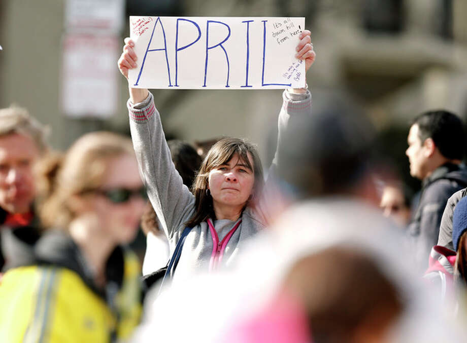 Justine Franco of Montpelier, Vt., holds up a sign near Copley Square in Boston looking for her missing friend, April, who was running in her first Boston Marathon Monday, April 15, 2013. Two bombs exploded near the finish line of the marathon on Monday, killing at least two people and injuring at least 23 others. (AP Photo/Winslow Townson) / FR170221 AP