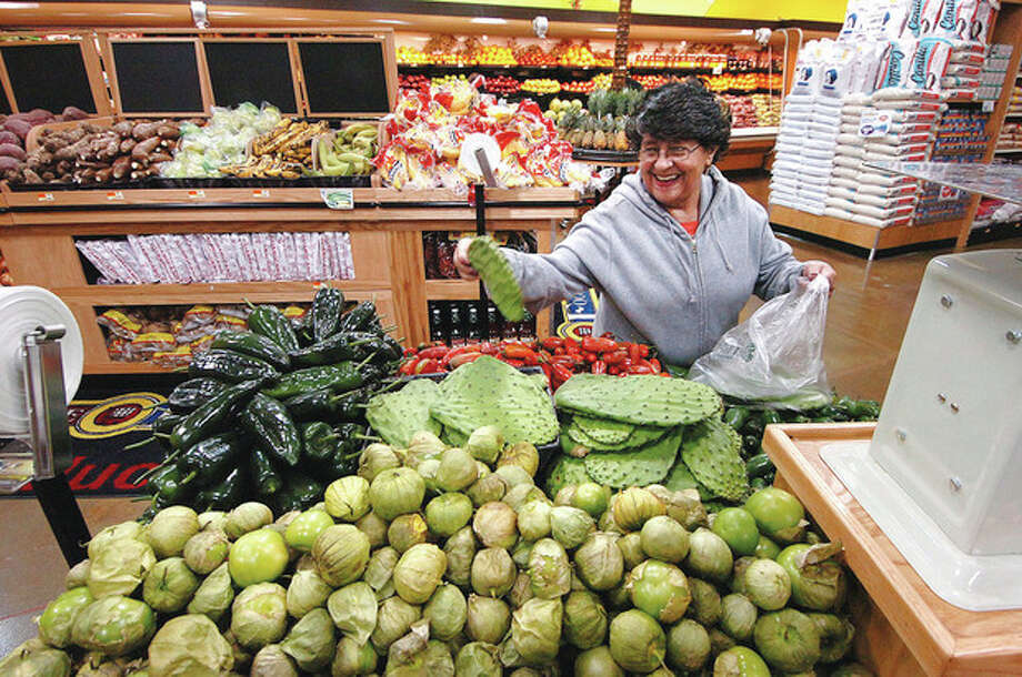 Photo/Alex von Kleydorff. Maria Lopez selects some Nopal in the produce section of Compare Foords in SONO. / © 2010 The Hour Newspapers/Alex von Kleydorff