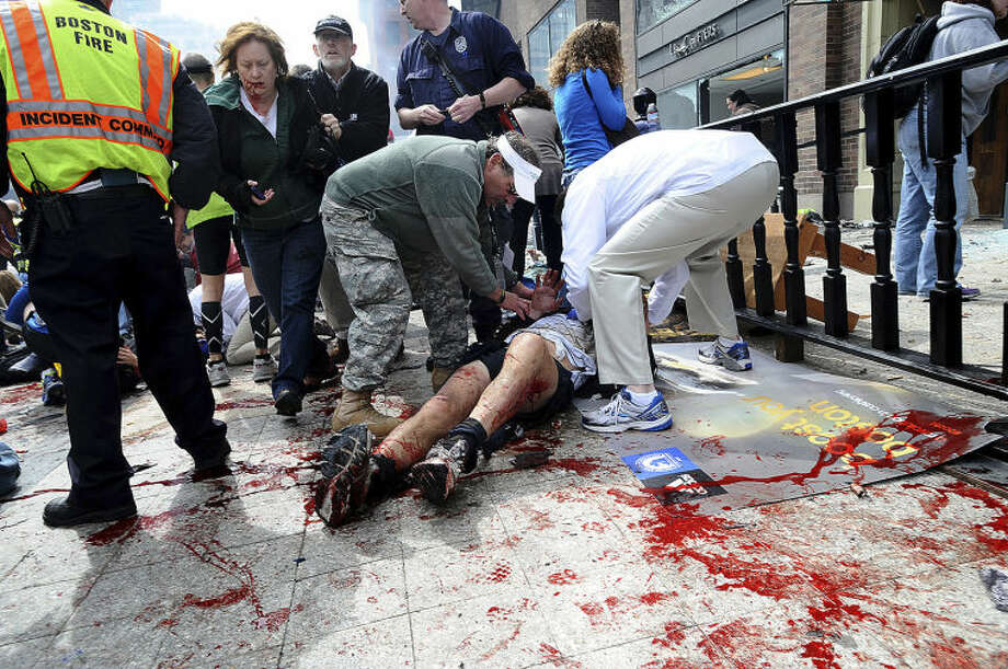 An injured person is helped on the sidewalk near the Boston Marathon finish line following an explosion in Boston, Monday, April 15, 2013. (AP Photo/MetroWest Daily News, Ken McGagh) MANDATORY CREDIT