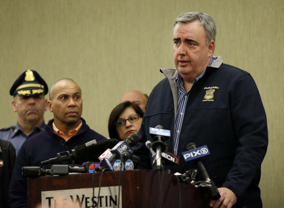 Boston Police Commissioner Ed Davis speaks as Massachusetts Gov. Deval Patrick listens, second from left, at a news conference in Boston Monday, April 15, 2013 regarding two bombs which exploded in the street near the finish line of the Boston Marathon on Monday, killing three people and injuring more than 130. (AP Photo/Elise Amendola)