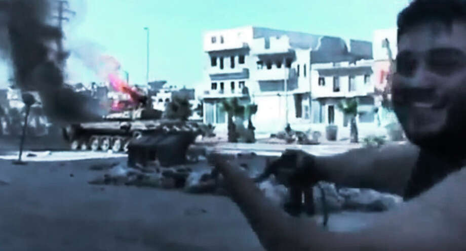 In this image made from amateur video released by the Ugarit News and accessed Monday, July 23, 2012, a Free Syrian Army soldier points toward a military tank, background, caught on fire during clashes with Syrian government troops in Aleppo, Syria. The Syrian regime acknowledged for the first time Monday that it possessed stockpiles of chemical and biological weapons and said it will only use them in case of a foreign attack and never internally against its own citizens. Aleppo, Syria's biggest city with about 3 million residents, has been the focus of rebel assaults by a newly formed alliance of opposition forces called the Brigade of Unification. (AP Photo/Ugarit News via AP video) TV OUT, THE ASSOCIATED PRESS CANNOT INDEPENDENTLY VERIFY THE CONTENT, DATE, LOCATION OR AUTHENTICITY OF THIS MATERIAL / Ugarit News