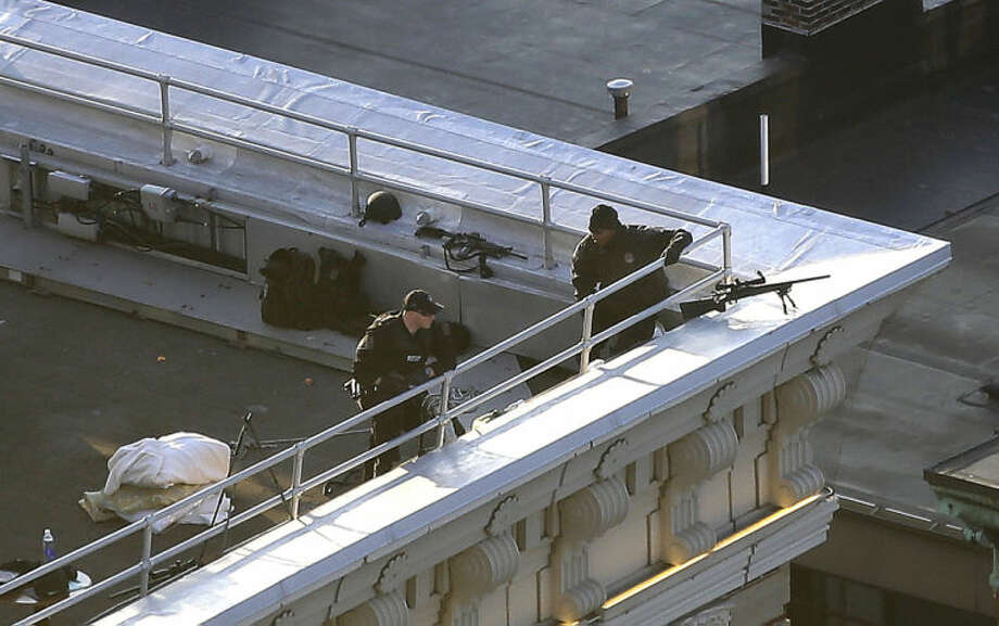 Two police officers have rifles and watch from the roof of the Lenox Hotel overlooking the finish area of the 2013 Boston Marathon in Boston Monday, April 15, 2013. Two bombs exploded earlier in the packed streets near the finish line of the Boston Marathon killing two people and injuring more than 80 others. (AP Photo/Elise Amendola)