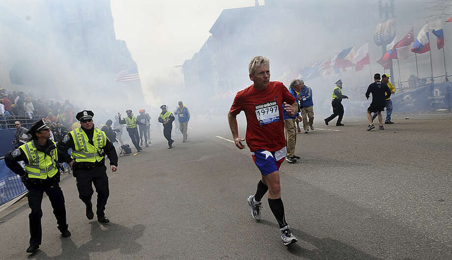 A Boston Marathon competitor and Boston police run from the area of an explosion near the finish line in Boston, Monday, April 15, 2013. (AP Photo/MetroWest Daily News, Ken McGagh) MANDATORY CREDIT