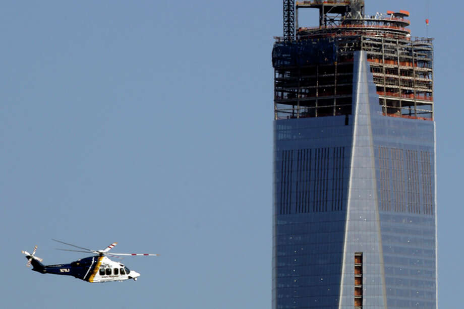 A New Jersey State Police helicopter flies by the construction site of One World Trade Center in Manhattan seen from The Heights neighborhood of Jersey City, N.J., Monday, April 15, 2013. New York is securing its city in the wake of explosions near the finish line at the Boston Marathon. (AP Photo/Julio Cortez) / AP