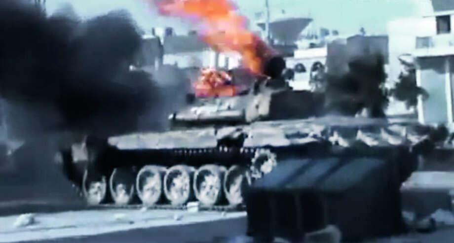 In this image made from amateur video released by the Ugarit News and accessed Monday, July 23, 2012, a Syrian military tank catches on fire during clashes with Syrian government troops in Aleppo, Syria. The Syrian regime acknowledged for the first time Monday that it possessed stockpiles of chemical and biological weapons and said it will only use them in case of a foreign attack and never internally against its own citizens. Aleppo, Syria's biggest city with about 3 million residents, has been the focus of rebel assaults by a newly formed alliance of opposition forces called the Brigade of Unification. (AP Photo/Ugarit News via AP video) TV OUT, THE ASSOCIATED PRESS CANNOT INDEPENDENTLY VERIFY THE CONTENT, DATE, LOCATION OR AUTHENTICITY OF THIS MATERIAL / Ugarit News