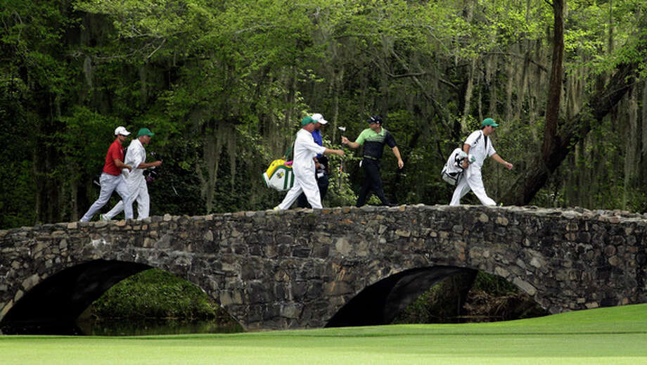 From left, Adam Scott, of Australia, Angel Cabrera, of Argentina, and Sergio Garcia, of Spain, walk across the Nelson Bridget with their caddies during the first round of the Masters golf tournament Thursday, April 11, 2013, in Augusta, Ga. (AP Photo/Matt Slocum) / AP