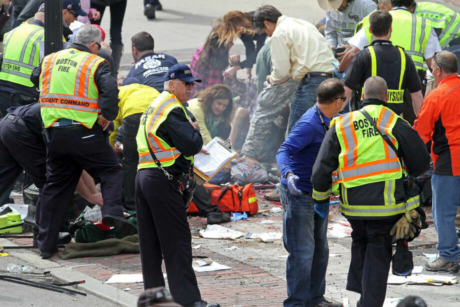 Rescue personnel aid injured people near the finish line of the 2013 Boston Marathon following explosions in Boston, Monday, April 15, 2013. Two explosions shattered the euphoria of the Boston Marathon finish line on Monday, sending authorities out on the course to carry off the injured while the stragglers were rerouted away from the smoking site of the blasts. (AP Photo/The Boston Herald, Stuart Cahill)