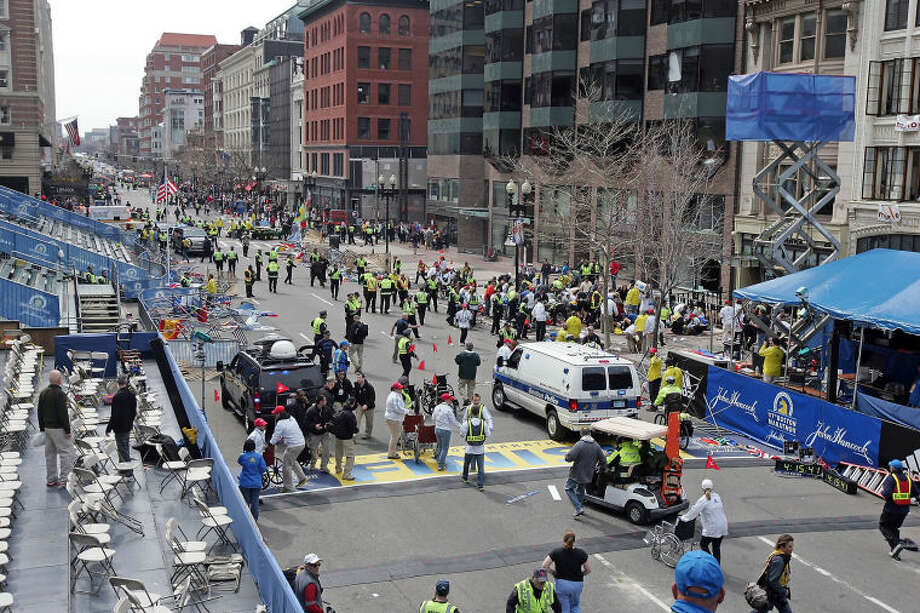 People react to an explosion at the 2013 Boston Marathon in Boston, Monday, April 15, 2013. Two explosions shattered the euphoria of the Boston Marathon finish line on Monday, sending authorities out on the course to carry off the injured while the stragglers were rerouted away from the smoking site of the blasts. (AP Photo/The Boston Herald, Stuart Cahill) BOSTON GLOBE OUT; METRO BOSTON OUT; MAGS OUT;
