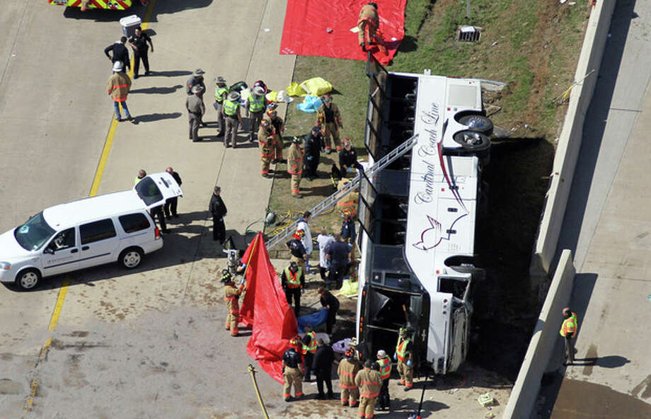 Rescue personnel work the scene of a Cardinal Coach Line charter bus accident on State Highway 161 in Irving, Texas on Thursday, April 11, 2013. Authorities say at least two people are dead and several injured after the chartered bus overturned. (AP Photo/The Dallas Morning News, Louis DeLuca) MANDATORY CREDIT; MAGS OUT; TV OUT; INTERNET OUT; AP MEMBERS ONLY / The Dallas Morning News
