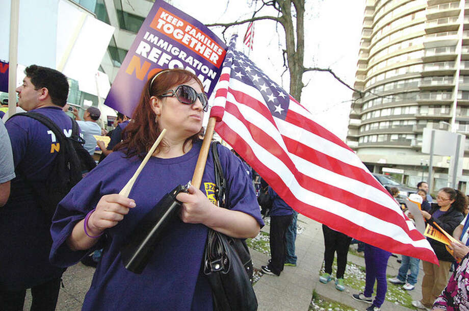 Hour Photo/Alex von KleydorffSonia Suarez with American flag and cowbell takes part in an immigration march and rally at the Government Center in Stamford Wednesday. / 2013 The Hour Newspapers
