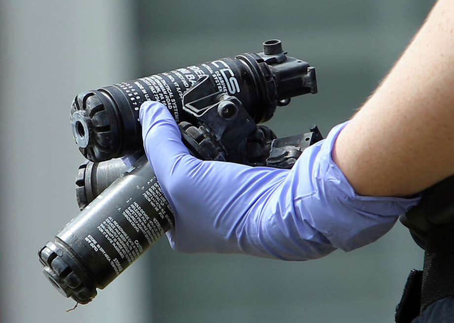 A Gwinnett County Police Department crime scene investigator carries a handful of used stun grenades Thursday afternoon, April 11, 2013, outside the Suwanee, Ga., house where Lauren Brown held firefighters hostage the night before. (AP Photo/Atlanta Journal Constitution, Ben Gray) GWINNETT OUT MARIETTA OUT / Atlanta Journal-Constitution