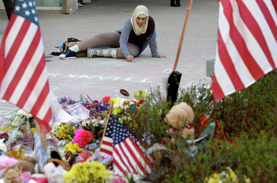Massachusetts Institute of Technology student Hajar Boughoula of Bizerte, Tunisia, writes a message on the ground with chalk near a makeshift memorial for fallen MIT police officer Sean Collier on the school's campus in Cambridge, Mass., Monday, April 22, 2013. Collier was fatally shot on the MIT campus Thursday, April 18, 2013. Authorities allege that Boston Marathon bombing suspects Tamerlan and Dzhokhar Tsarnaev were responsible. (AP Photo/Steven Senne) / AP