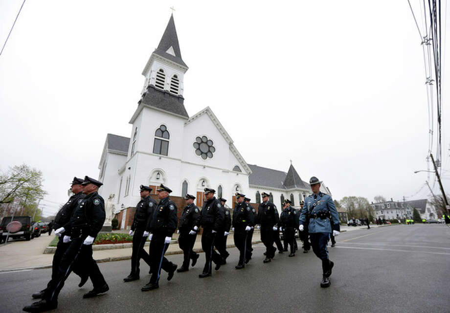 Massachusetts Institute of Technology police officers march as they depart St. Patrick's Church in Stoneham, Mass., following a funeral Mass for MIT police officer Sean Collier, Tuesday, April 23, 2013. Collier was fatally shot on the MIT campus Thursday, April 18, 2013. Authorities allege that the Boston Marathon bombing suspects were responsible. Law enforcement official at right is unidentified. (AP Photo/Steven Senne) / AP