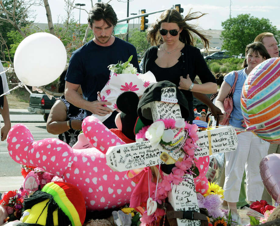 """Actor Christian Bale and his wife Sibi Blazic view a cross and large display of flowers and stuffed animals dedicated to Veronica Moser-Sullivan, 6, the youngest of the 12 victims of Friday's mass shooting, Tuesday, July 24, 2012, at a memorial in Aurora, Colo. Twelve people were killed when a gunman opened fire during a late-night showing of the movie """"The Dark Knight Rises,"""" which stars Bale as Batman. (AP Photo/Ted S. Warren) / AP"""