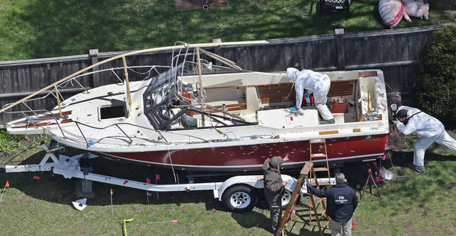 Investigators from the FBI inspect the boat where Boston Marathon bombing suspect Dzhokhar Tsarnaev was found hiding on Friday night in a backyard in Watertown, Mass., Tuesday, April 23, 2013. There is blood spattered on the wheel fender of the trailer and bullet holes in the hull of the boat. Tsarnaev had gunshot wounds to the head, neck, legs and hands when he was captured hiding out in the boat on Friday night, April 19, 2013. (AP Photo/The Boston Globe, David L. Ryan) BOSTON HERALD OUT; QUINCY OUT; NO SALES / The Boston Globe