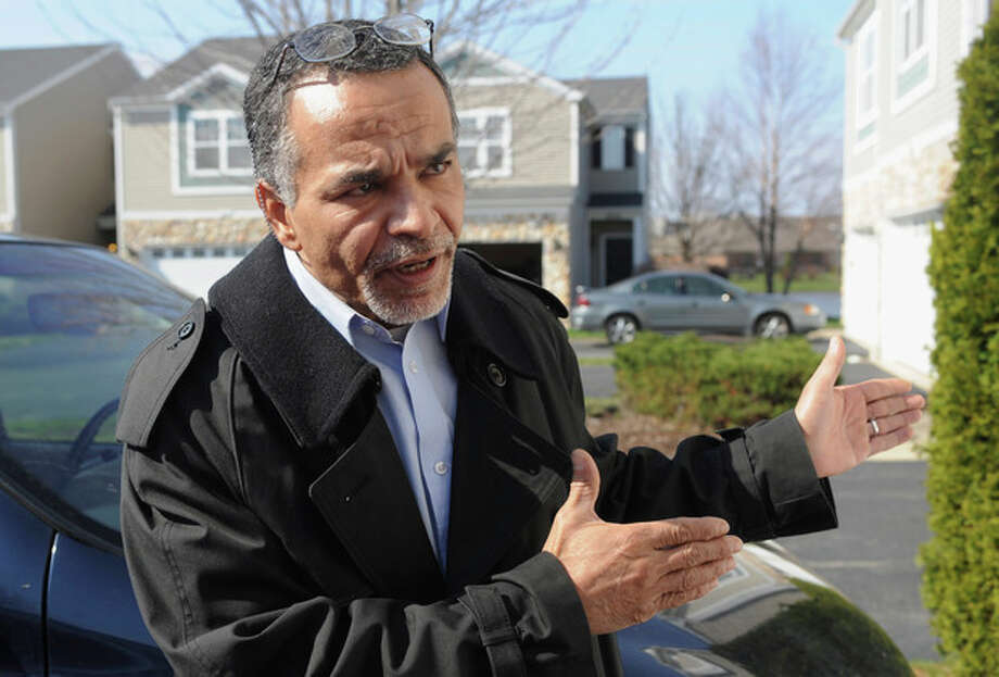 In this Sunday, April 21, 2013 photo, Ahmad Tounisi, whose 18-year-old son Abdella Ahmad Tounisi is charged with attempting to provide material support to terrorism, speaks to a reporter outside his home in Aurora, Ill. Abdella Ahmad Tounisi was arrested by the FBI on Friday, April 19 as he prepared to board a plane to Turkey at O'Hare International Airport. He is scheduled to appear at federal court in Chicago Tuesday, April 23, 2013. (AP Photo/The Beacon-News, Steven Buyansky) CHICAGO LOCALS OUT / The Beacon-News