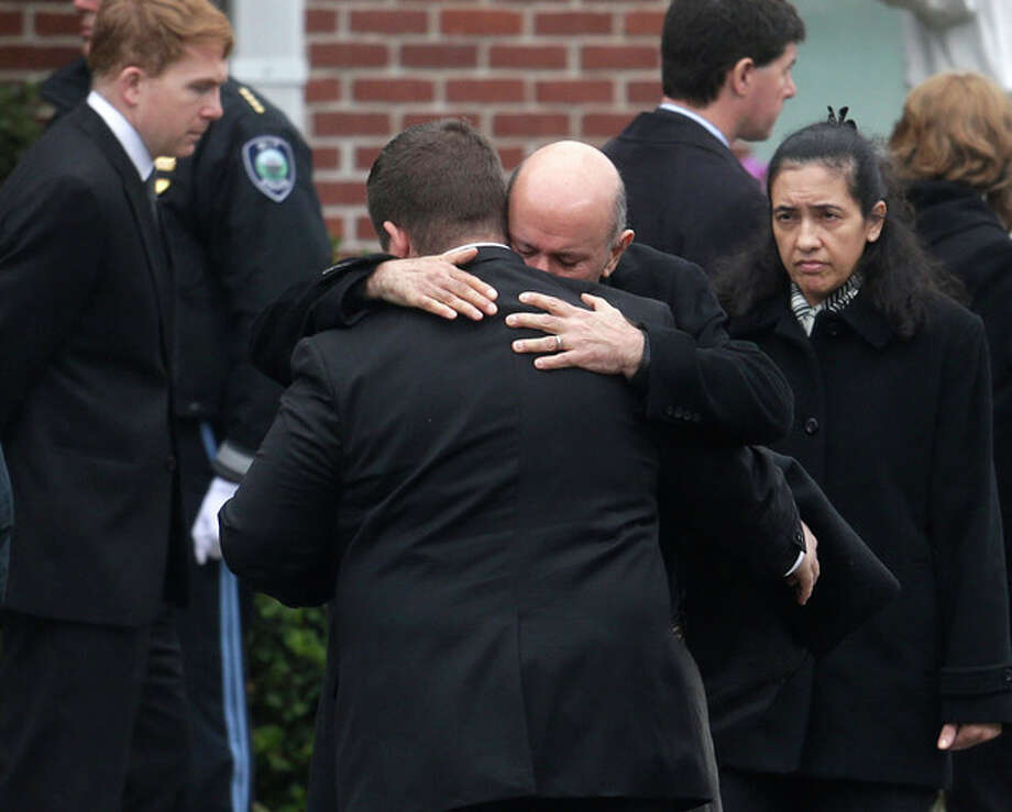 Mourners hug as they depart St. Patrick's Church in Stoneham, Mass., following a funeral Mass for Massachusetts Institute of Technology police officer Sean Collier, Tuesday, April 23, 2013. Collier was fatally shot on the MIT campus Thursday, April 18, 2013. Authorities allege that the Boston Marathon bombing suspects were responsible. (AP Photo/Steven Senne) / AP