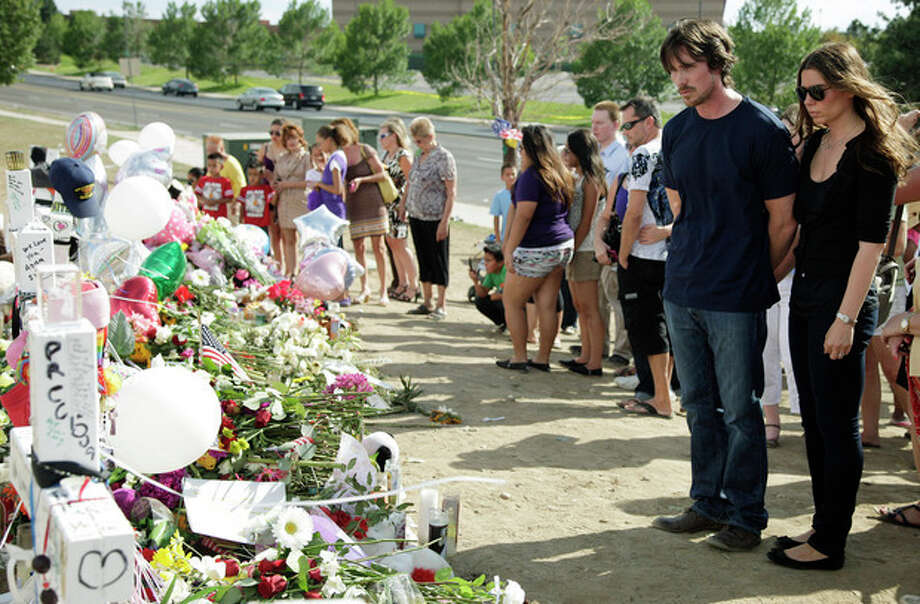 "Actor Christian Bale and his wife Sibi Blazic visit a memorial to the victims of Friday's mass shooting, Tuesday, July 24, 2012, in Aurora, Colo. Twelve people were killed when a gunman opened fire during a late-night showing of the movie ""The Dark Knight Rises,"" which stars Bale as Batman. (AP Photo/Ted S. Warren) / AP"