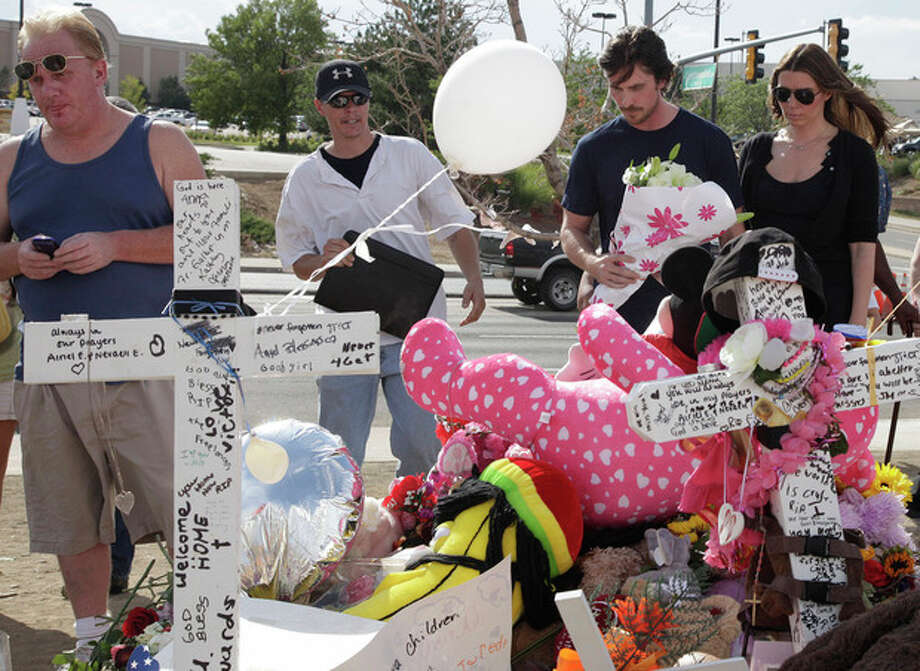 """Actor Christian Bale and his wife Sibi Blazic, at right, carry flowers to place on a memorial to the victims of Friday's mass shooting, Tuesday, July 24, 2012, in Aurora, Colo. Twelve people were killed when a gunman opened fire during a late-night showing of the movie """"The Dark Knight Rises,"""" which stars Bale as Batman. (AP Photo/Ted S. Warren) / AP"""