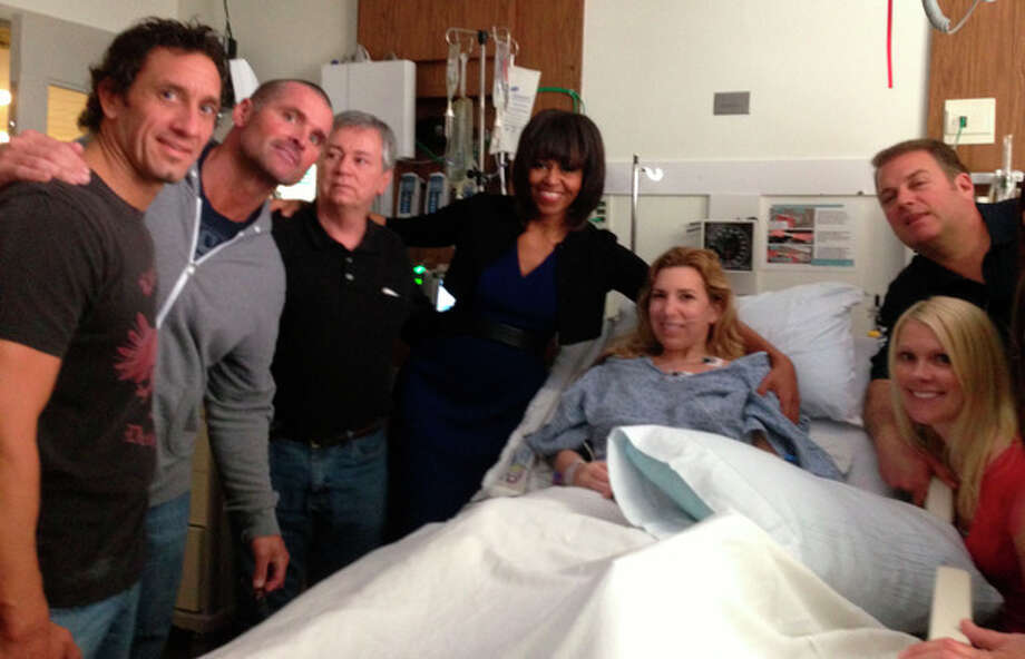 This April 18, 2013 photo provided by Alfred Colonese shows from left Alfred Colonese, Mick Henn, Dale Abbott, first lady Michelle Obama, Heather Abbott, Jason Geremia, and Michelle Dalrymple at Brigham and Women's Hospital in Boston. Heather Abbott was scrambling to get off the sidewalk when the force of the second blast blew her through the restaurant doorway. The day of the bombings, Abbott and a half-dozen friends took in the traditional Patriots' Day Red Sox game at Fenway Park. They left the match early and headed to Forum, where former New England Patriots were gathered to raise money for offensive guard Joe Andruzzi's cancer foundation, and where another friend was tending bar. (AP Photo/Courtesy of Alfred Colonese) / Alfred Colonese