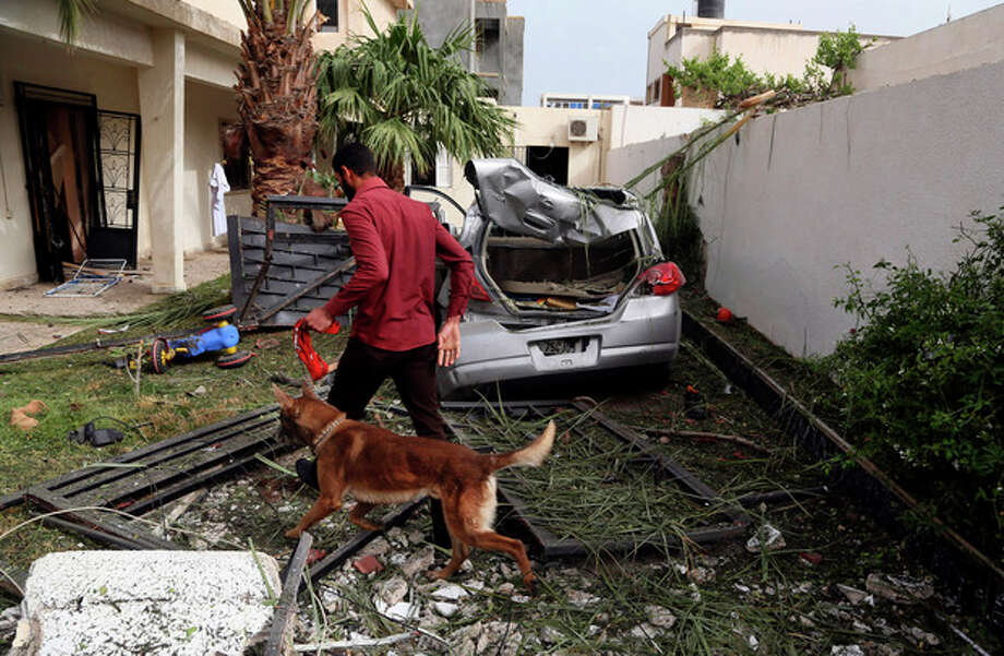 A security officer using a sniffer dog inspects the site of a car bomb that targeted the French embassy wounding two French guards and causing extensive material damage in Tripoli, Libya, Tuesday, April 23, 2013. The explosives-laden car was detonated just outside the embassy building in Tripoli's upscale al-Andalus neighborhood, officials said. (AP Photo/Abdul Majeed Forjani) / AP