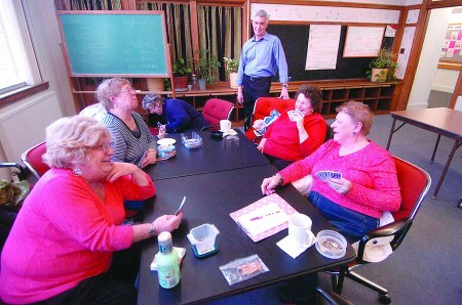 Photo/Alex von Kleydorff. Norwalk Senior Center Executive Director Paul Palumbo stops by the activities room as a the ladies play their regular card game of Five Crowns
