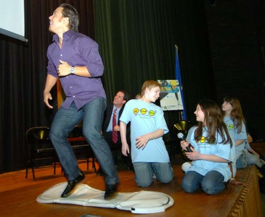 Photo/Alex von Kleydorff. Apolo Ohno trys his skill at a computer running game on the big screen during his visit to Cloonan Middle School.