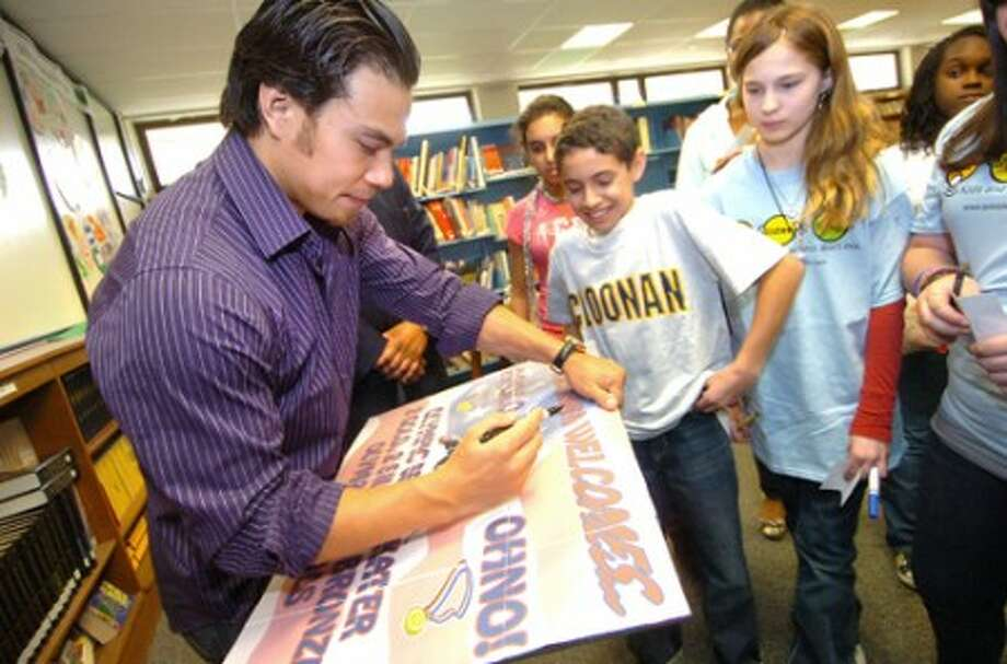 Photo/Alex von Kleydorff. Apolo Ohno signs a hand made poster while visiting with some of the scholar students before a program at Cloonan Middle school